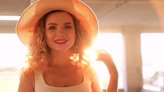 Close up view of Pretty Young Woman Standing Outdoor at Sunset. Looking Stylish. Posing like a Model. Portrait of Girl with Beautiful Make up. Wearing Straw Hat. Red Lips. Curly Blond Hair.