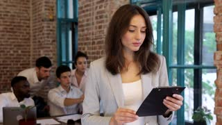 Close up view of Pretty Young Woman Wearing Classical Suit. Standing in the Foreground. Holding Office Tablet with Papers. Charming Smile. Interethnic Group of Business People in the Background.