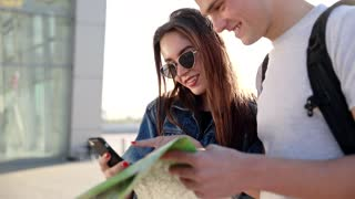 Close up view of Stylish Woman and Handsome Man. Couple Travelling to Foreign City with Map. Peolpe Standing near the Airport. Wearing Casual Clothes. Enjoying Time at Sunset. Pleasant Mood.