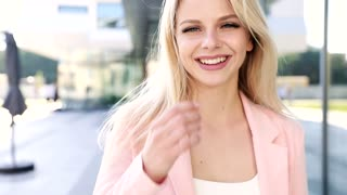 Close up view of Woman's Face Looking at the Camera. Posing, Smiling Blond Girl. Young Model. Slow Motion. Stylishly Dressed. Enjoying her Lifestyle. Businesswoman in the City.