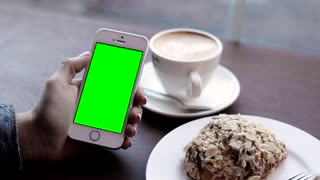 Close up view of Woman's Hands Holding Smartphone. Fingers Sliding on Green Screen. Swiping Left, Right. Clicking, Scrolling on the Display. Girl Sitting at the Cafe. Dessert and Coffee on the Table.