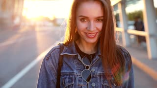 Close up view of Young Trendy Woman at Sunset. Pretty Girl Looking at the Camera. Walking like a Model. Slow Motion. Smiling Happily. Looking Satisfied. Gentle Look with Flirt. Posing on Camera.