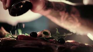 Extreme close up view of a tattooed man's hand seasoning cooked meat with pepper, salt, olives, rosemary in bright light. Preparation process, cooking, delicious cuisine.