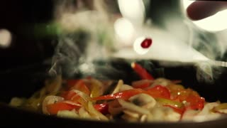 Extreme close up view of male hands adding red hot peppers to the frying dish. Spicy taste, secret recipe, gourmet food. European cuisine. Slow motion, camera stabilizer shot