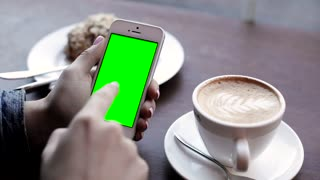 Girl Holding Modern Mobile in her Hands. Woman Using a Smartphone. Sliding on Green Screen. Swiping Left, Right. Gestures of Zooming. Sitting at the Cafe. Delicious Cake, Coffee in the Background.