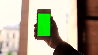 Hands Holding Modern White Smartphone in the Centre of the Shot. Fingers Sliding on Green Screen. Swiping Left, Right. Gestures of Zooming on Touchscreen. Mobile Digital Device.