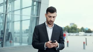 Handsome Businessman Chatting on his Smartphone While Exiting the Big Building. Checking News, Mails. Looking Confident, Successful. Classically Dressed. Walking in the City.