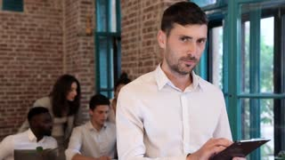 Handsome Businessman Working on the Digital Tablet. Standing inside the Modern Office. Looking at the Camera. Office Workers Standing at the Table in the Background. Business People. Slow Motion.