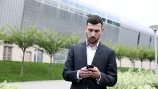 Handsome Confident Businessman Walking through the Park in the City. Wearing Classical Suit. Using his Mobile Phone. Serious Conversation on it. Business Lifestyle.