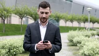 Handsome Young Businessman Walking through the Park. Smiling Happily. Typing on his Mobile Phone. Official Dressed. Huge Modern Building in the Background. Successful life.