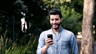 Handsome Young Man Using his Modern Smartphone Outdoor. Checking News on it. Walking in the Street lined with Green Trees. Great Mood. Bearded Turkish Man. Slow Motion. Casual Outfit.