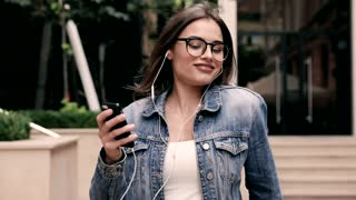 Happily Smiling Young Woman Enjoying her Life. Listening to the Music. Using Headphones. Girl Dancing in the Street. Casual Outfit. Stylish Jeans Jacket. Charming Smile. Holding Smartphone.