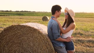 Happy Couple Enjoying Free Time Together. Handsome Man and Beautiful Woman Leaning on Round Bales of Hay. Resting on Harvested Field. Romantic Mood. Positive Emotions. Evening Walk.