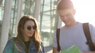 Happy Couple Travelling to Foreign City. Walking near the Airport. Young Attractive Woman Using her Mobile Device. Handsome Man Browsing Tourist Map. Looking for Direction. Casully Dressed.