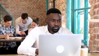 Male Afroamerican Working at the Office. Sitting at the Table with Modern Computer. Looking at the Screen, Camera. Smiling Sincerly. Young Man Working on Start up. Business People in the Background.