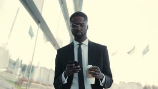 Man holds Coffee-To-Go, uses Phone while walking by the Business Center. Young Businessman in a suit and stylish Glasses have Coffee Break, successful lifestyle.