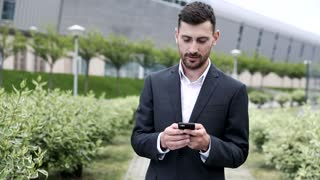 Officially Dressed Young Businessman Standing in the Park. Typing on his Mobile Phone. Alley Planted with Bushes. Huge Modern Building in the Background. Successful Lifestyle.