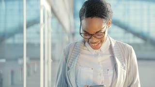 Portrait of Happy Afroamerican Businesswoman using Smartphone near Business Building. Attractive Woman walking in the City at the Break and working on her Mobile Phone. She has Suit and Glasses.