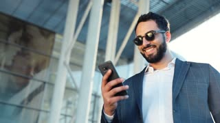 Portrait of Multinational Businessman using Mobile Phone for Social Network. Business Building on the Background. Classical Suit Dressed on. Business Lifestyle. Attractive People. Smartphones User.