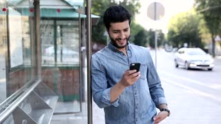 Portrait of Young Bearded Man Standing on the Bus Stop in the big City. Holding his Modern Smartphone. Checking Time on his Wristwatch. Waiting for his Transport. Slow Motion. Street Style.