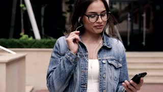 Pretty Brunette Woman Walking in the Street. Singing while Listening to Music. Enjoying her Life. Happily Smiling Girl. Wearing Stylish Jeans Jacket. Holding her Smartphone. Casual Outfit.