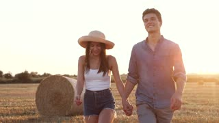 Pretty Woman Wearing Straw Hat Walking with her Beloved Man Outside. Couple of Lovers Holding Hands Together. Enjoying their Time on the Farm. Smiling Sincerly. Having Romantic Mood.