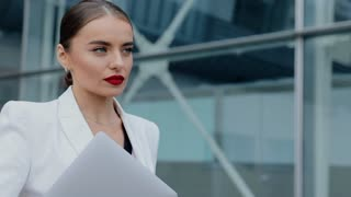Professional Businesswoman in white Suit with Laptop Walking in the City. Business building in the background. Steadicam Shot. Successful Lifestyle. Classical Dressed. Professional Businesswoman.