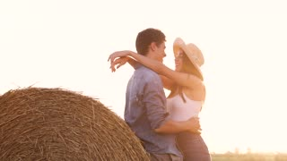 Romantic Farm Couple Spending Time Together. Lovers Meeting on Harvested Field. Standing near Haystack. Attractive Woman Hugging Handsome Man. Rural Style. Enchanting Nature. Slow Motion.