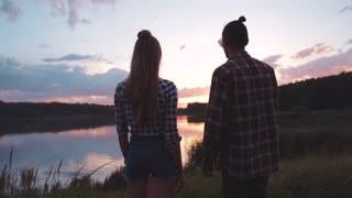 Romantic Young People in casual outfit standing by the lakeside, Holding Their Hands, looking at each other, enjoying the scenery. Romantic Date, Relationship Goals. Happy Together.