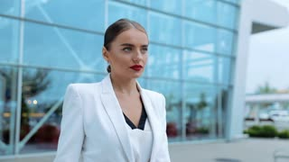 Serious Businesswoman Walking in the City with Red Lipstick in white modern Suit. Business building on the background. Slow Motion. Business Lifestyle. Classical Dressed. Fashion Businesswoman.