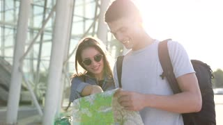 Smiling Loving Couple Walking in the Foreign City. Young Trendy Woman Drinking Delicious Coffee. Handsome Man Holding Tourist Map. People Smiling Sincerly. Huge Glass Airport in the Background.