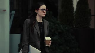 Strictly young business woman in classical grey jacket on walking through city with Laptop. She has black shirt and glasses on. She has hair choices.