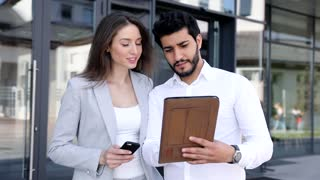 Successful Business People Standing by the Office Building. Couple of Business Partners Working on the Tablet. Using Digital Devices for Work. Classically Dressed. Looking Confident.