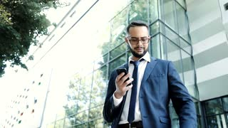 Successful Young Businessman Standing near Modern Office. Using his Smartphone. Chatting on it. Wearing Stylish Clothes. Looking at his Luxury Wristwatch. Rich Lifestyle. Bearded Man. Multi ethnical