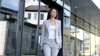 Trendy Businesswoman Taking a Walk down the Street. Holding Mobile Phone in her Hands. Classically Dressed. Charming Smile. Looking Serious, Confident. Business Lifestyle.