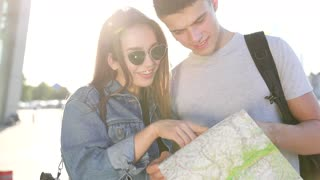 Trendy Woman and Handsome Man Standing by the Airport. Young Girl Explaining Direction to Attractive Man. Browsing the map Together. Foreign City. Pleasant Mood. Slow Motion.