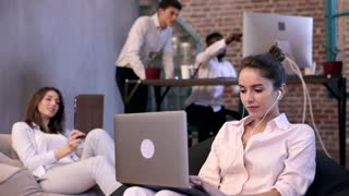 Two Young Businesswomen Sitting in the Chair Bag. Using Laptop, Digital Tablet. Talking Online. Business People Working on Start up in the Background. Interethnic Group. Slow Motion.