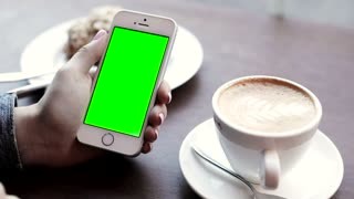Woman Sitting at the Cafe. Delicious Cake, Coffee on the Table. Girl Holding Modern Smartphone in her Hands. Making Finger Gestures. Clicking on Green Screen, Touching Display.