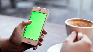 Woman Sitting at the Cafe Drinking Tasty Coffee. Holding Mobile Device with green Screen. Touching Display with her Fingers. Making Gestures of Zooming. Clicking on Screen. Swiping Left, Right.