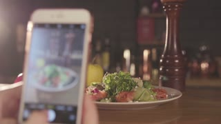 Woman's hand is Taking Photo of the dish on her modern Mobile Phone. Salad, Pepper shaker , Colorful Peppers are in the background. Modern Apps, Technologies, Nice photos for Social Networks.