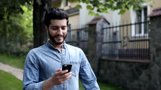 Young Attractive Man Wlaking through the City. Showing his Emotions. Smiling Sincerly. Holding his Mobile Phone. Chatting in the Social Networks. Bearded Turkish Man. Casual Outfit.