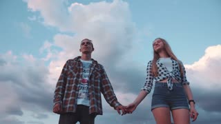 Young Couple in Love Holding their Hands, she looks at him, Smiling Happily. Wonderful Sky on the background. Casual stylish wear. Romantic atmosphere, Feeling Good. Slow motion.