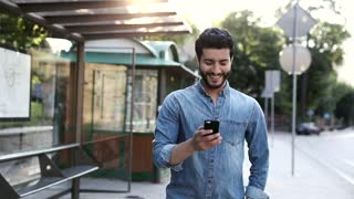 Young Handsome Bearded Man Walking in the Big City at Sunset. Smiling Happily. Wearing Casual Clothes. Walking near the Bus Stop. Using his Mobile Phone. Chatting in the Social Networks.