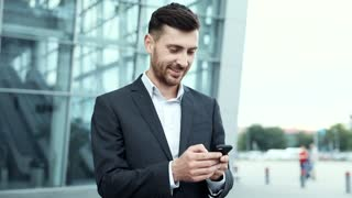 Young Handsome Man Wearing Elegant Suit. Checking Mails on his Smartphone. Working on it while Standing near Office. Attractive Bearded Businessman. Business Lifestyle.