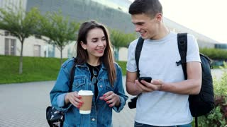 Young Happy Couple Walking in the Park. Woman is Drinking Tasty Coffee. Man Carries a Modern Camera. Showing something on his Smartphone. Smiling Couple. Airport Building in the Background.