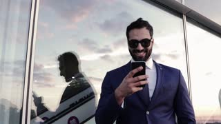 Young man stands outside the glass building and uses his phone for texting, internet surfing. Stylish look, successful lifestyle. Modern technologies, being online.