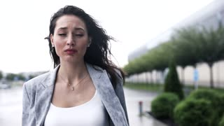 Young Pretty Businesswoman Walking in th City While it is Raining. Looking at the Sky. Feeling Sad and Depressed. Wet Clothes. Beautiful Woman in Despair. Having some Problems.