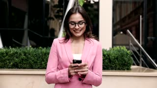 Young Pretty Woman Walking by the Huge Glass Building. Smiling Happily. Walking with her Mobile Phone. Classically Dressed Girl. Stylish Hairstyle. Pleasant Mood. Nice Weather. Business Life.