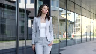 Young Successful Businesswoman Taking a Walk near the Office Building. Looking Stylish, Serious. Wearing Classical Suit. Confident Gait. Business Lifestyle. Pretty Woman.