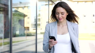 Young Successful Businesswoman Walking in the City. Chatting on her Mobile Device. Surfing the Internet. Stylish Outfit. Woman with Charming Smile. Slow Motion. Business Lifestyle.